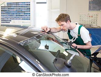 Worker in glaziers workshop installs windshield - Glazier...