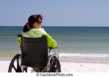 Woman Disability Beach - Handicapped woman sits disabled in...
