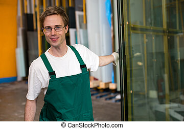 Glazier in workshop handling glass - Worker in glazier's...