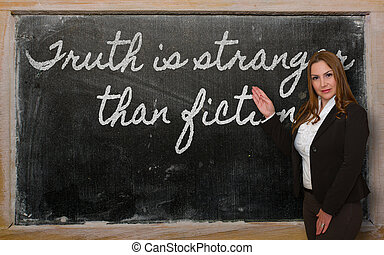 Teacher showing Truth is stranger than fiction on blackboard...