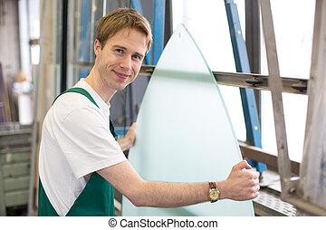 Worker in glazier's workshop handling glass - Glazier...