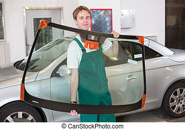 Glazier with car windshield made of glass - Glazier handling...