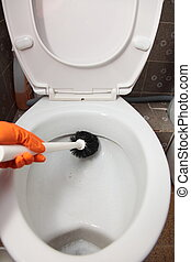 Gloved hand cleaning toilet bowl using brush - Female hand...