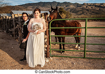 Same Sex Couple by Horse - Smiling bride with same sex groom...