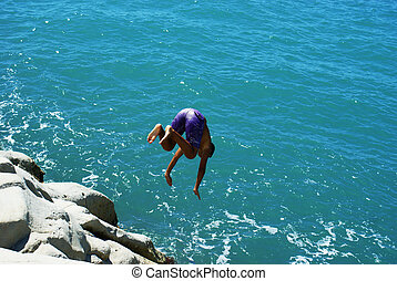 acrobatic dive from cliff in the clear water of Scala dei...