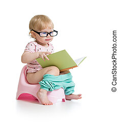 baby girl sitting on chamberpot with book