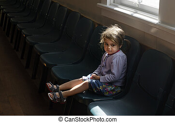 Child Abuse - Little girl sit on a chair in empty hallway of...