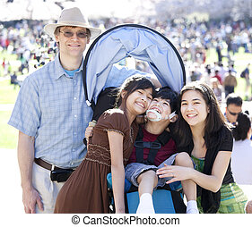 Large multiracial family in crowd with disabled child in...