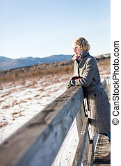 Girl on the bridge in the field during a winter day
