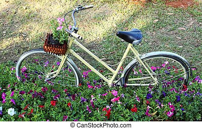 old bicycle with flowers in the front basket,parked in the...