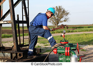 oil worker with wrench check pipeline