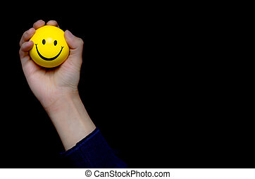 Male hand holding a yellow smiley ball emoticon with a big...
