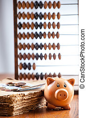 Piggy bank on old book - Piggy bank by old book with...