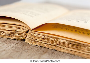 Close up of an old opened book on a wooden surface