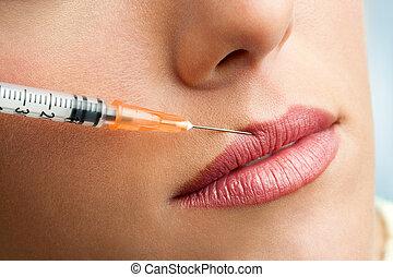 Macro botox syringe on female lips. - Close up of syringe...