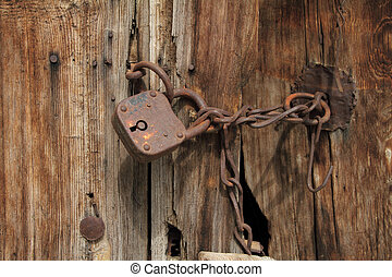 Old rusty padlock with chain on wooden door