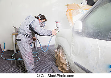 Car body painter spraying paint on bodywork parts - Car body...