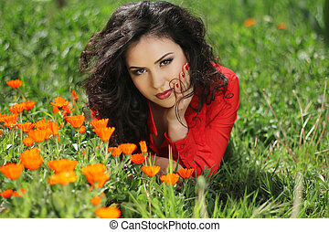 Woman in red resting on green grass, outdoors portrait