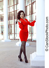 Beautiful woman model posing in red dress over architecture...