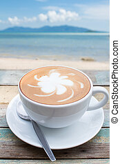 Coffee cup on terrace facing seascape