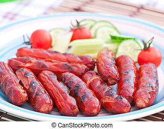 grilled sausages on the grill and a salad of fresh...