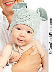 Mother holding baby with knitted cap