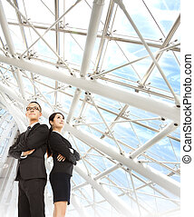 young businessman and businesswoman stand in the modern office