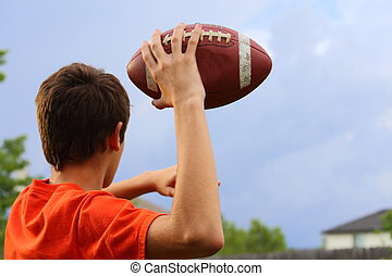Throwing Football - A young man cocking his arm back and...
