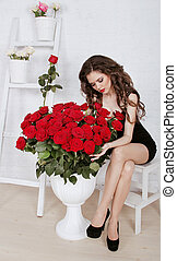 Beautiful young woman with bouquet of red roses in modern...