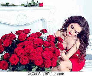 Sexy brunette woman with bouquet of red roses in modern...