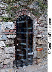 Door grille in an old brick wall - Ancient door grill in the...