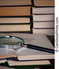 Magnifying glass on a pile of open books Concept of...
