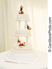 Wedding cake closeup at reception is white with bride and...