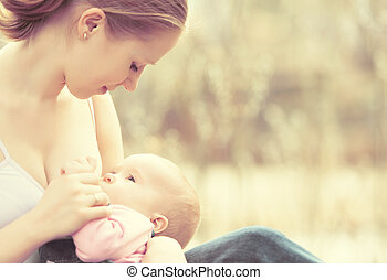 mother feeding her baby in nature outdoors in the park -...