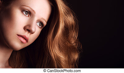 sad, melancholy girl with long red hair on a dark background...