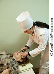 Ophthalmologist measures the eye pressure