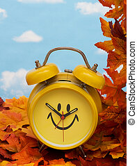 Fall Back Time Change - Fall leaves with yellow clock on sky...