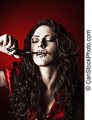 Horror shot: strange girl with mouth sewn shut cutting the...