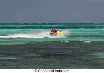 Father and daughter riding a jet ski.