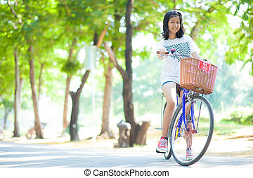 Young woman bicycling Within the park The space allocated...