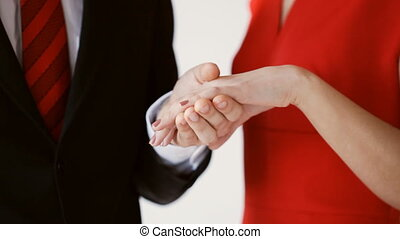 groom putting a wedding ring to bride's hand - closeup of...