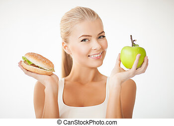woman with apple and hamburger - picture of sporty woman...