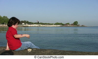 Child  throwing stones into the sea - Summer holiday