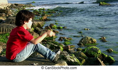 Little boy throwing stones into the sea