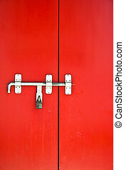 Iron lock on the red door - old iron lock with bolt on the...