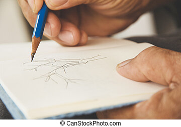 man writing on sketchbook