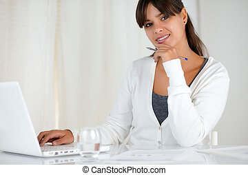 Smiling young woman looking at you using laptop - Portrait...