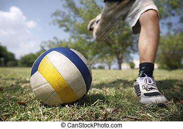 Kids playing soccer game, young boy hitting ball in park -...