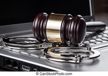 handcuffs and judge gavel on computer concept - handcuffs...