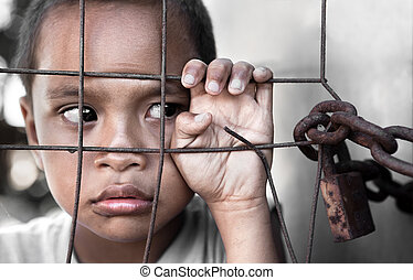boy behind fence - young Asian boy behind fence, slight...